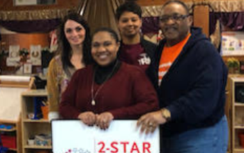 Staff from The Word Youth Center hold their 2-star rating sign
